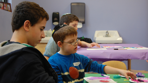 Ari spends his Sunday afternoons volunteering at Friendship Circle. In this picture Ari does a crafts project together with his buddy Gavi.