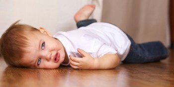 little kid crying lying on floor
