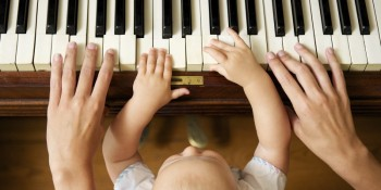 baby playing piano with mom
