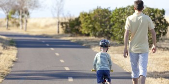 kid on bike with dad walking