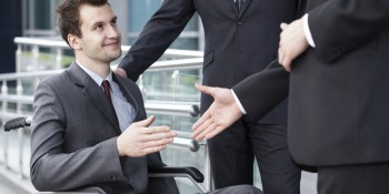 Close-up of a disabled businessman shaking hand with business partners