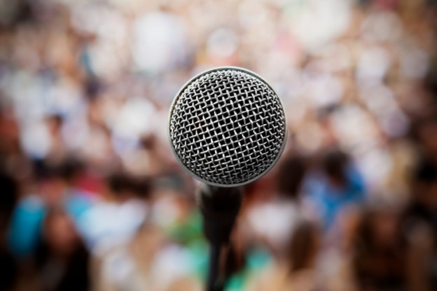 Close up of a microphone in front of an audience