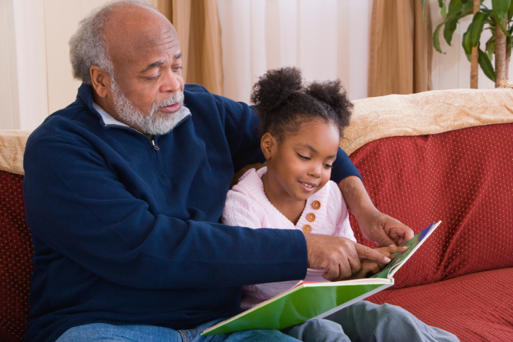 Grandfather reading with granddaughter