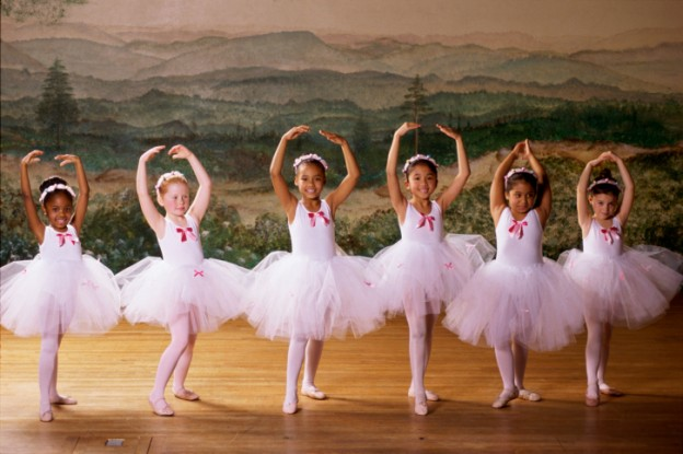 Group of ballet dancers dancing with their arms raised