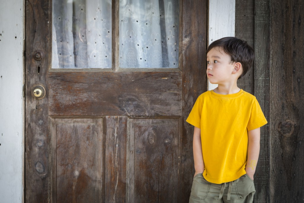 Melancholy Mixed Race Boy Standing In Front of Door