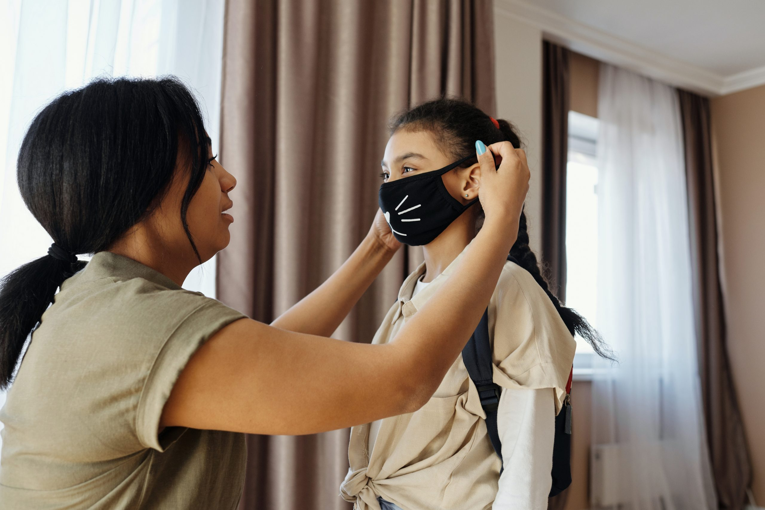 Mother putting COVID-19 mask on daughter